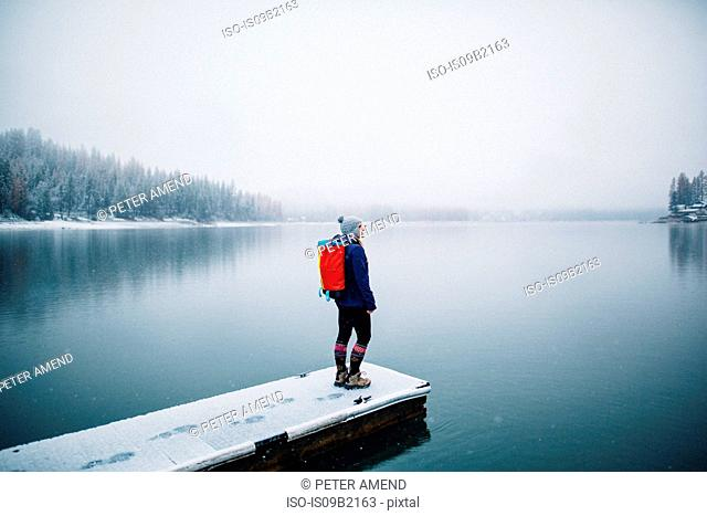 Hiker on snow covered pier looking at view of lake, Bass Lake, California, USA