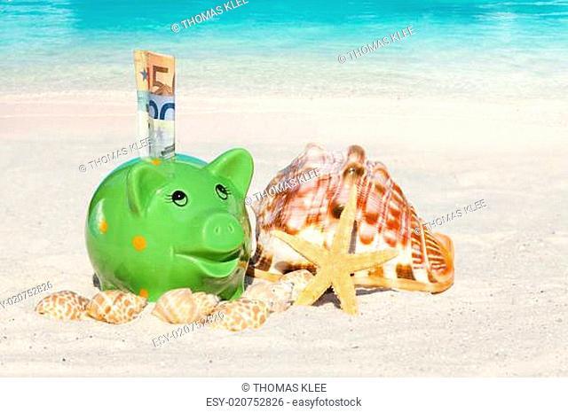 Grünes Sparschwein mit Geldscheinen am Sandstrand