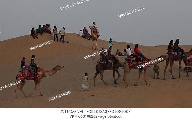 Tourists riding camels on Sam dunes in Desert National Park in the Great Thar Desert,near Jaisalmer, Rajasthan, India