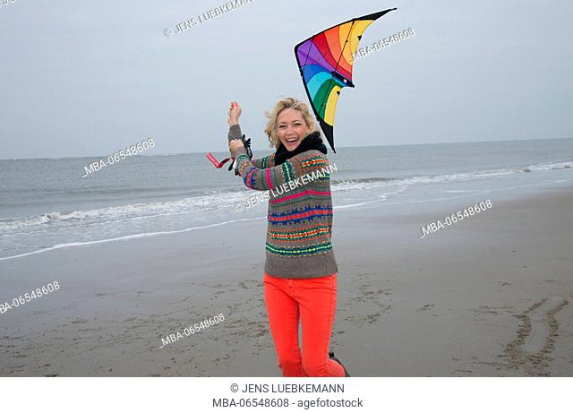 Woman running in the direction of camera on the beach holding a stunt kite