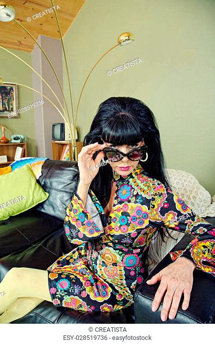 Groovy woman in 1960s fashion looking over sunglasses