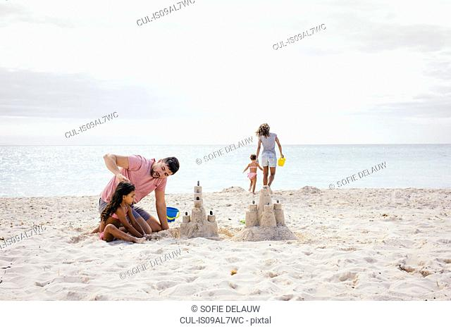 Couple and two girls building sandcastle on beach, Tuscany, Italy