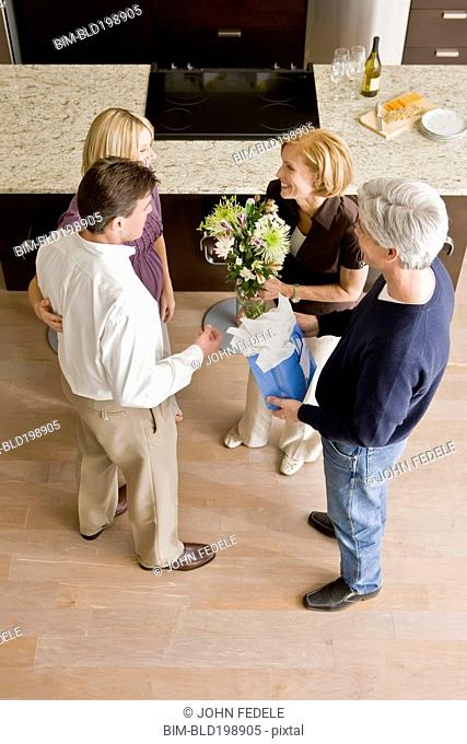 Caucasian couple giving hosts gift and flowers