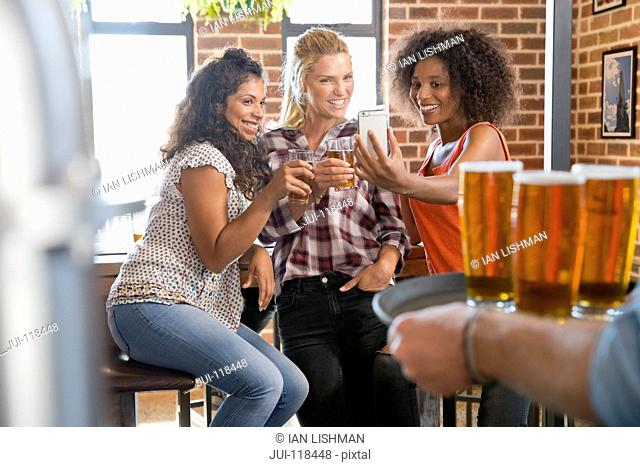 Three Female Friends In Bar Posing For Selfie On Mobile Phone