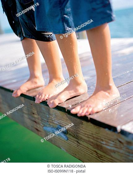 Boys standing at the edge of wooden pier, close up