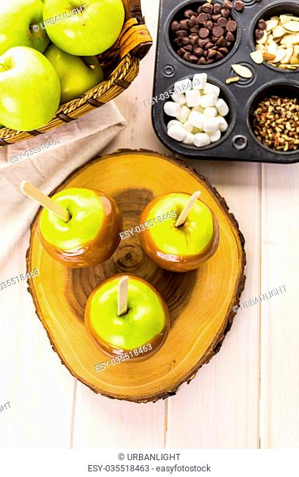 Apples freshly dipped in caramel on cutting board