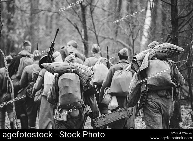 Re-enactors Dressed As World War II Russian Soviet Red Army Soldiers Marching Through Forest In Autumn Day. Photo In Black And White Colors