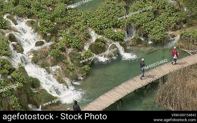 Plitvice Lakes, National Park, Dinaric Alps, Croatia, a UNESCO World Heritage Site, tourists on walkways walking by water cascades running between plants...