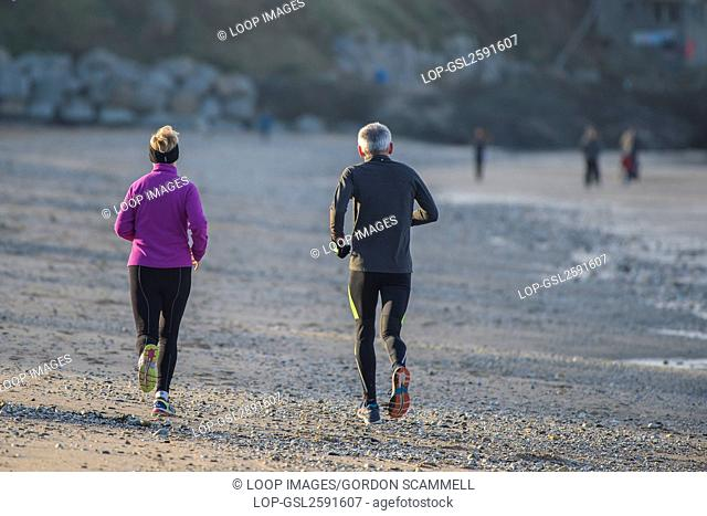 A mature couple run along Fistral beach at Newquay in Cornwall