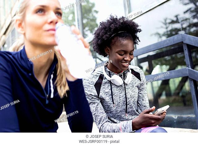 Two sporty young women relaxing after running in the city