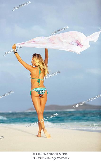 Professional kiteboarder Susi Mai on the beach enjoying the beautiful tropical white sands of the Caribbean; Necker Island, British Virgin Islands