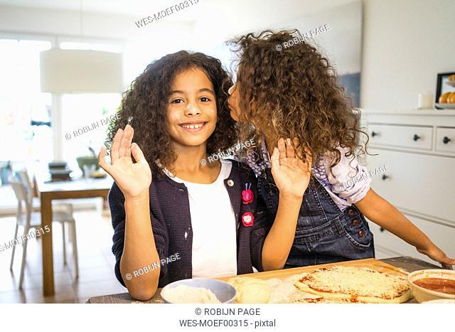 Little girl kissing sister in kitchen, baking pizza