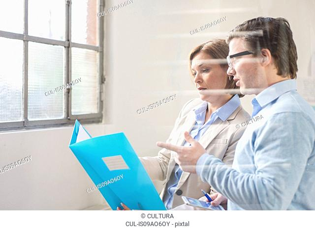 Businessman and woman reading file in office