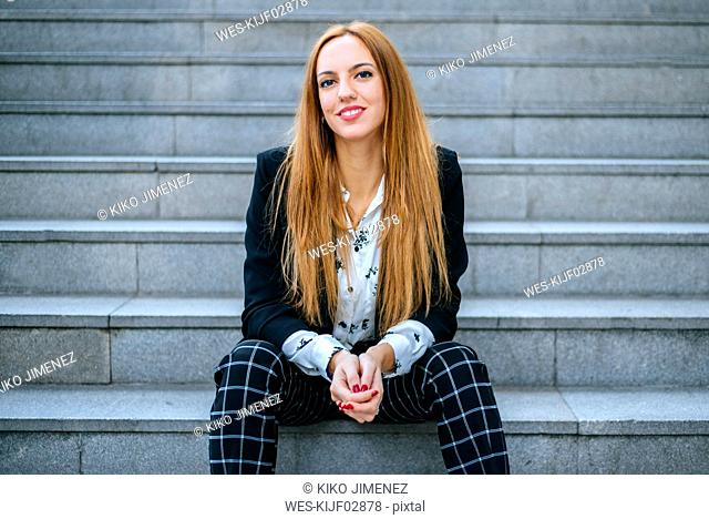 Portrait of smiling young woman sitting on stairs