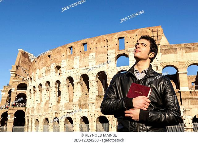 A young man stands holding a Bible and looks up with the Colosseum in the background; Rome, Italy