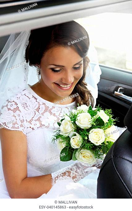 beautiful bride with a bouquet of roses sitting in the car