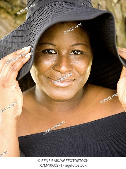 A black woman wears a hat for sun protection
