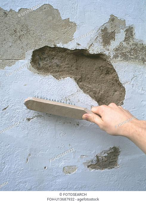 Hand using brush on damaged plaster wall