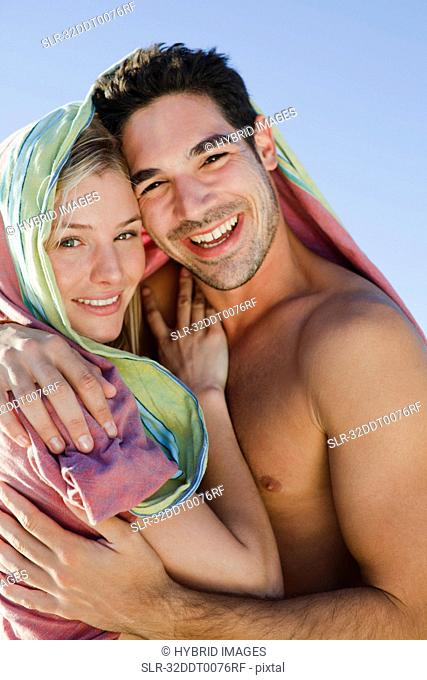 Couple hugging under blanket on beach