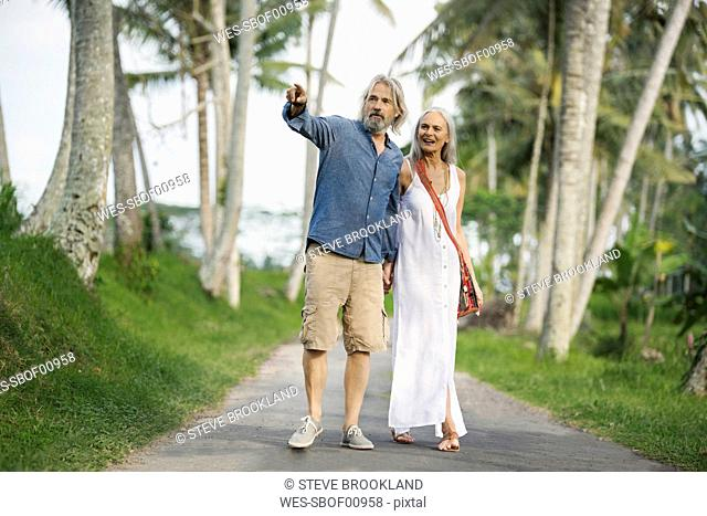 Handsome senior couple strolling through tropical landscape with palm trees