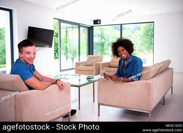 Young multiethnic couple sitting on a sofa in the luxury living room, using a tablet computer