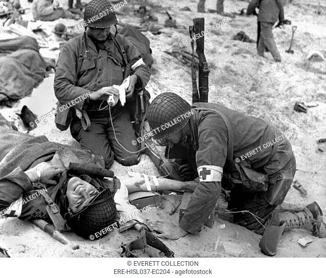 Medics treat a wounded U.S. soldier on D-Day. During the Normandy landings in Nazi occupied France, June 6, 1944, World War 2. (BSLOC-2014-2-37)