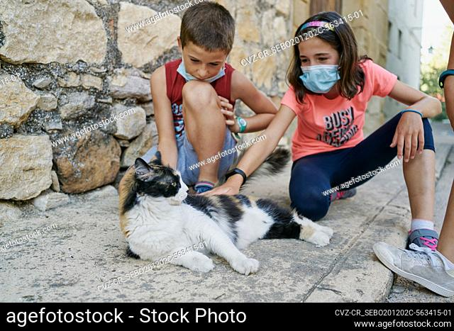 Two children with masks for the covid19 play with a black and white cat that is lying in the street