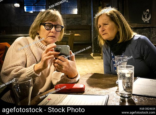 Two women look at photos on a phone in a pub at Silver Star ski resort near Vernon, BC, Canada