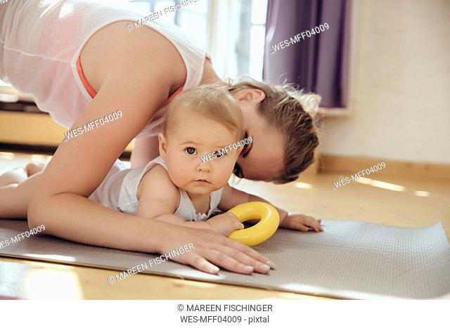 Mother kissing her baby while working out on a yoga mat