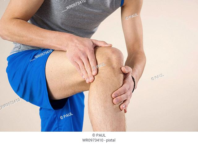 young man touching his knee