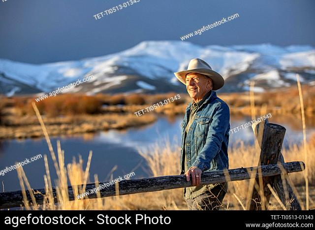 USA, Idaho, Sun Valley, Senior man leaning against fence looking at view