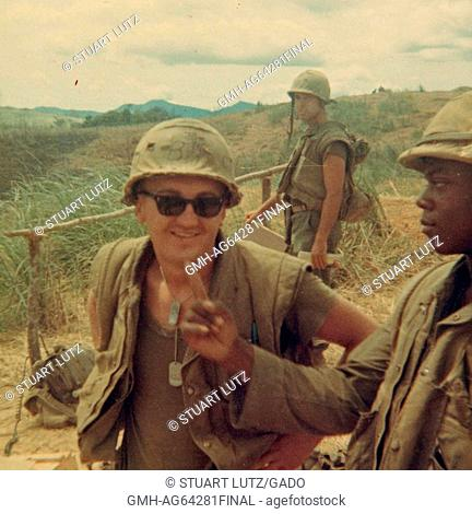 Marine in combat vest and helmet, wearing sunglasses and dog tag, standing in a field during the Vietnam war, an African-American fellow Marine pointing to him...