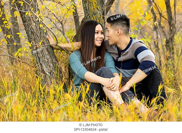A young Asian couple enjoying a romantic time together and sitting under a tree in a park in autumn; Edmonton, Alberta, Canada