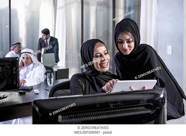 Middle Eastern businesswomen in office looking at digital tablet
