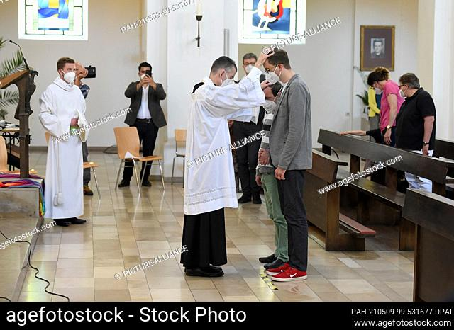 09 May 2021, Bavaria, Munich: Vicar Wolfgang Rothe blesses two men during a Catholic service with the blessing of homosexual couples as part of a nationwide...