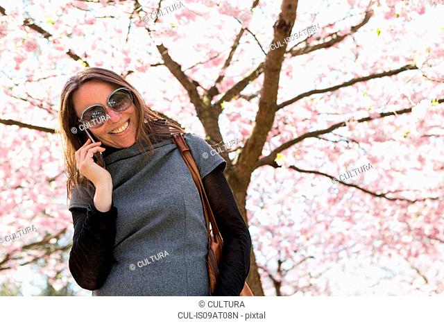 Mature woman chatting on smartphone in front of cherry blossom