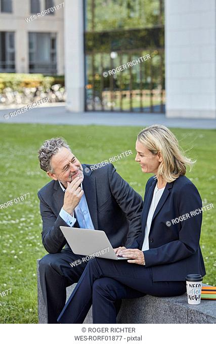 Businesswoman and businessman sitting on a wall in the city using laptop