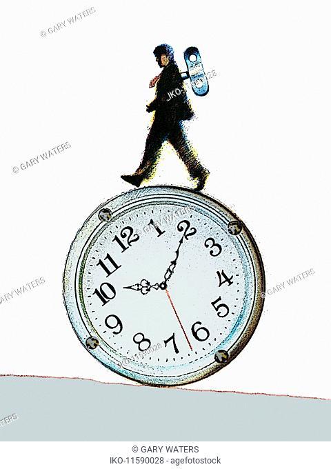 Wind-up businessman balancing on rolling clock