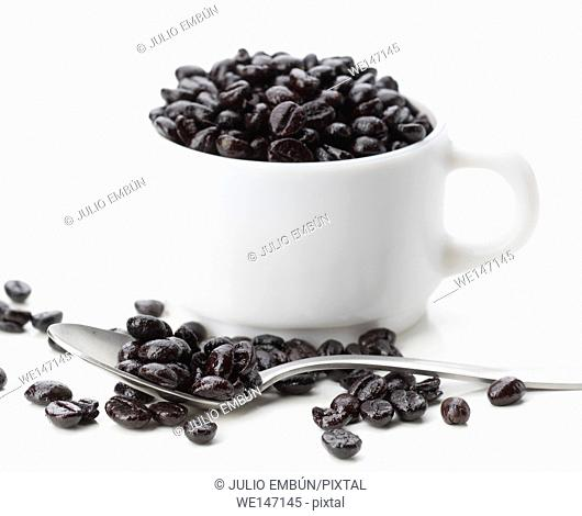 porcelain cup overflowing with roasted coffee beans, isolated on white
