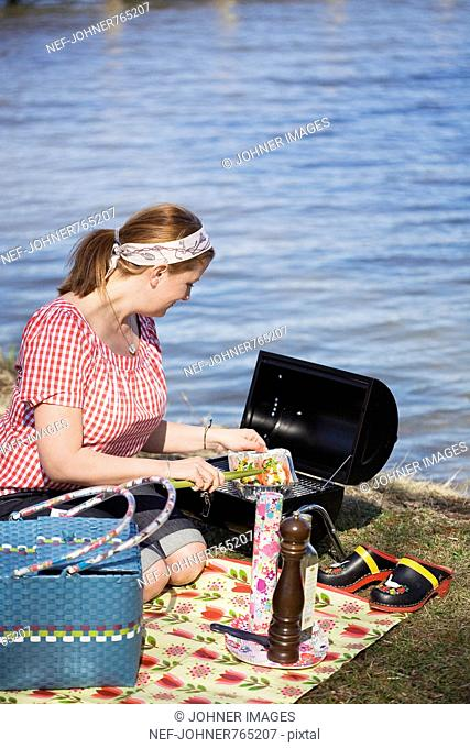 Woman grilling salmon by the water, Sweden