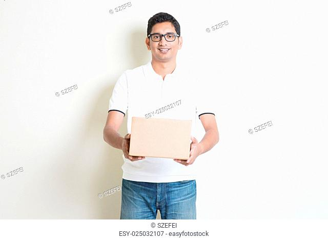 Courier delivery service concept. Indian man received a brown box, standing on plain background with shadow. Asian handsome guy model
