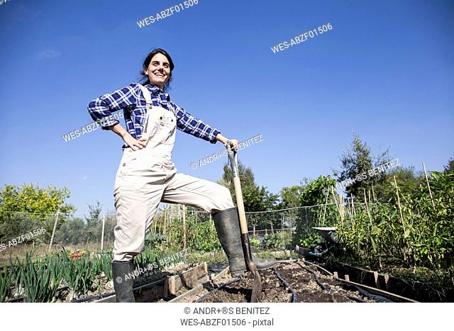 Woman working on farm, preparing vegetable patch
