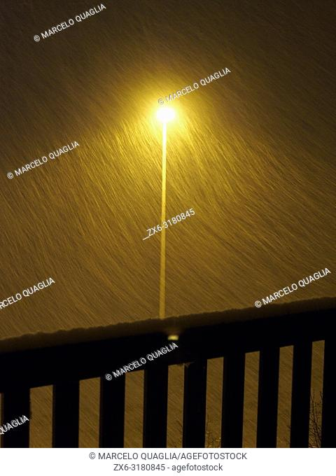 Snow storm and street lamp post at night. Santa Eulàlia village. Lluçanès region, Barcelona province, Catalonia, Spain