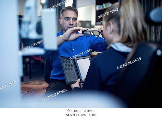 Optometrist doing eye test with girl
