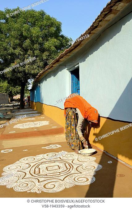 India, Rajasthan, Tonk region, Woman painting a floor Mandana with chalk powder