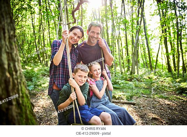 Portrait smiling family at rope swing in woods
