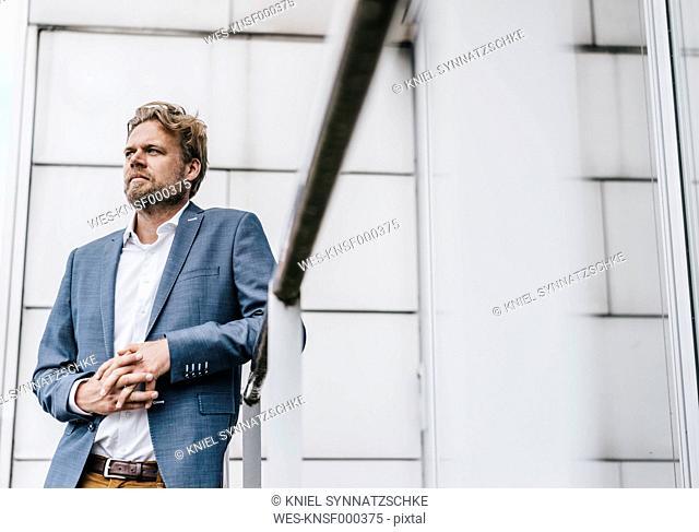 Businessman leaning on railing
