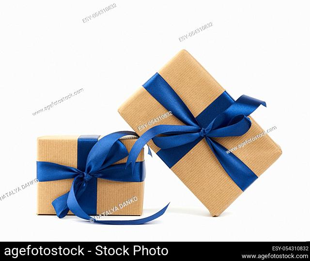 rectangle box wrapped in brown kraft paper and tied with a silk blue ribbon, gift isolated on a white background