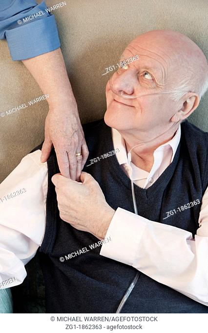 Elderly man with a carer or nurse offering a comforting hand of support