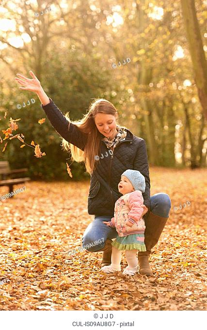 Mid adult woman and baby daughter watching autmn leaves in park